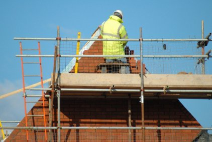 Man in high-vis jacket inspecting a roof